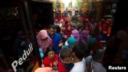 انڈونیشیا کے شہر سورابایا میں شہری کوڑے کے بدلے ٹکٹ حاصل کر کے بس میں سوار ہو رہے ہیں۔ فائل فوٹو