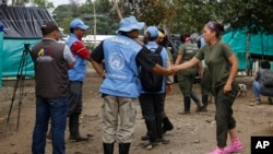 FILE - A United Nations observer shakes hands with a rebel of the Revolutionary Armed Forces of Colombia (FARC) before a meeting in La Carmelita, Colombia, March 1, 2017. A FARC splinter group on Wednesday released a U.N. contractor it had taken hostage in May.