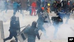 Seorang polisi anti huru-hara memukul seorang pemrotes dalam bentrokan di ibukota Kyiv (22/1).