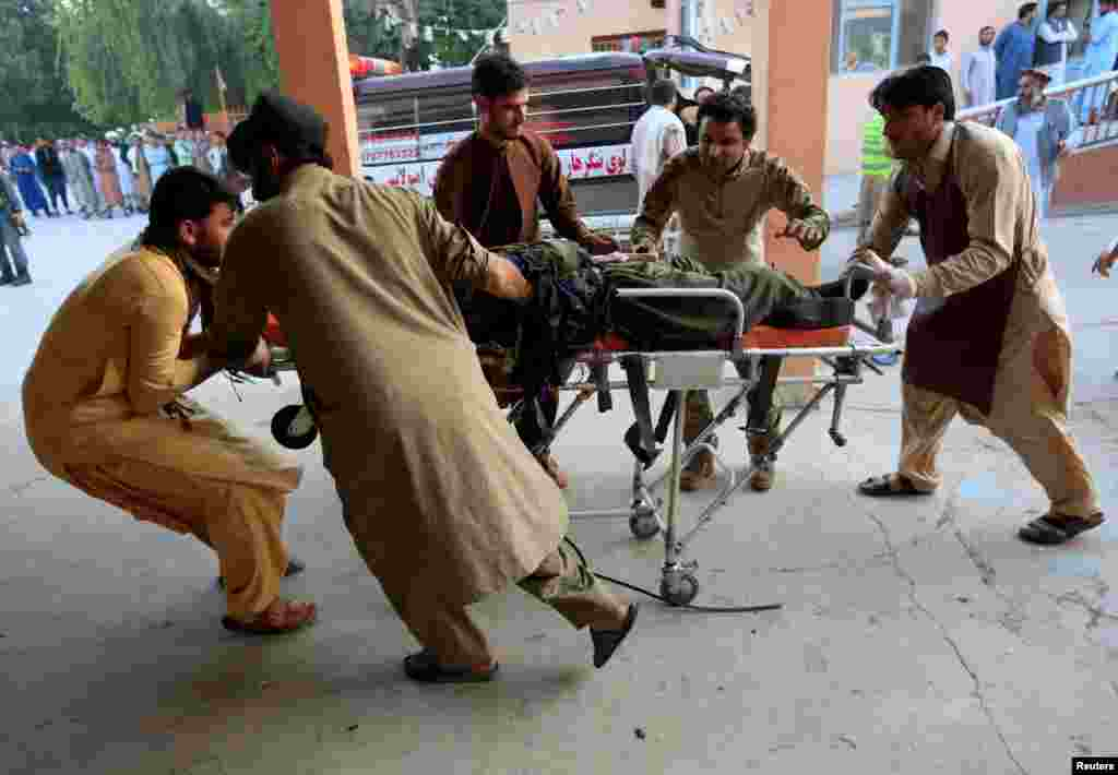 Men carry a wounded person to a hospital after an explosion in Jalalabad, Afghanistan.