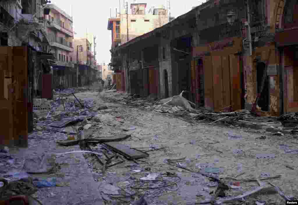 Damaged buildings and shops with members of the Syrian army patrolling in the distance in the old city of Aleppo, Syria, January 3, 2013.