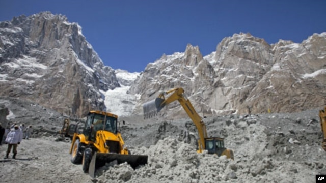 Pakistani soldiers use heavy machinery to dig through the snow at the site of an avalanche and landslide that struck a Pakistani army battalion headquarters, at the Siachen Glacier in Kashmir, April 18, 2012.