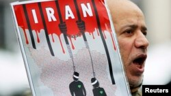 FILE - An Iranian exile shouts slogans to protest against executions in Iran during a demonstration in front of the Iranian embassy in Brussels on December 29, 2010.