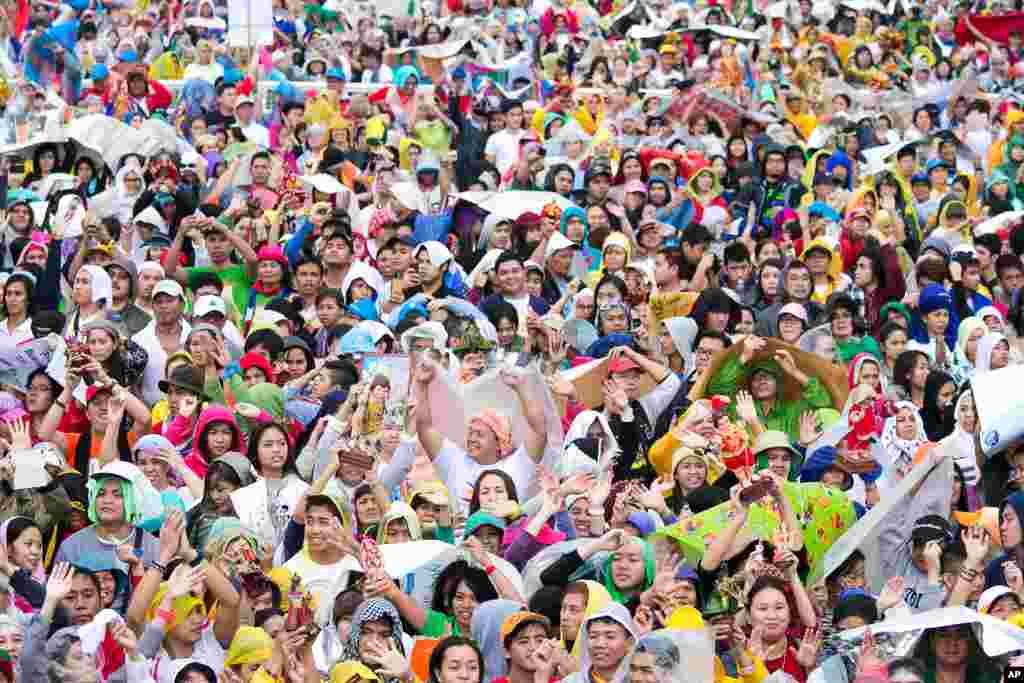 مردم فيليپين در مراسم نيايش در حضور پاپ فرانسيس در مانيل تصوير سانتو نينو (فرزند مقدس) را بر سر دست میگيرند.