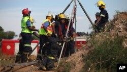 Спасатели пытаются оказать помощь пойманным в ловушку шахтерам.