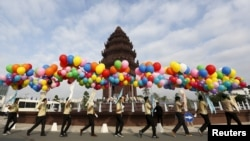 Students hold balloons as they walk past the Independence Monument during celebrations marking the 62nd anniversary of the country's independence from France in central Phnom Penh, Cambodia November 9, 2015. REUTERS/Samrang Pring - RTS631R