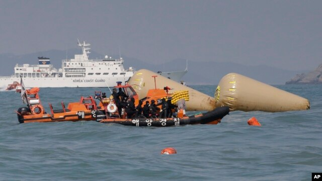 South Korean rescue team members on a boat approach to the buoys which were installed to mark the area of the sunken ferry Sewol in the water off the southern coast near Jindo, south of Seoul, South Korea, Sunday, April 20, 2014.