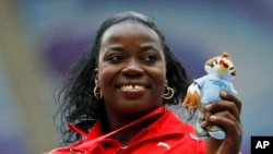 FILE - Cuba's Yarelys Barrios poses with her bronze medal for the women's discus throw during the medals ceremony at the World Athletics Championships in the Luzhniki stadium in Moscow, Russia, Aug. 12, 2013. She was stripped of the silver medal in the women's discus from the 2008 Beijing Olympics on Thursday after testing positive in a reanalysis of her doping samples.