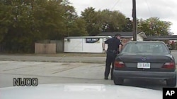 In this April 4, 2015, frame from dashboard video provided by the North Charleston Police Department, Patrolman Michael Thomas Slager stands by Walter Lamer Scott's car during a traffic stop in North Charleston, S.C.