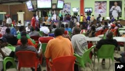 in this photo taken on Saturday, Jan. 18, 2014, punters monitor the screens after betting on horses and football in Harare, Zimbabwe. Poor and desperate Zimbabweans hang out in Harare's crowded low-end betting halls, placing stakes as low as U.S. 20 cents on world soccer matches and international horse and dog races with fervent hopes of getting quick returns on their bit of cash. (AP Photo/Tsvangirayi Mukwazhi)