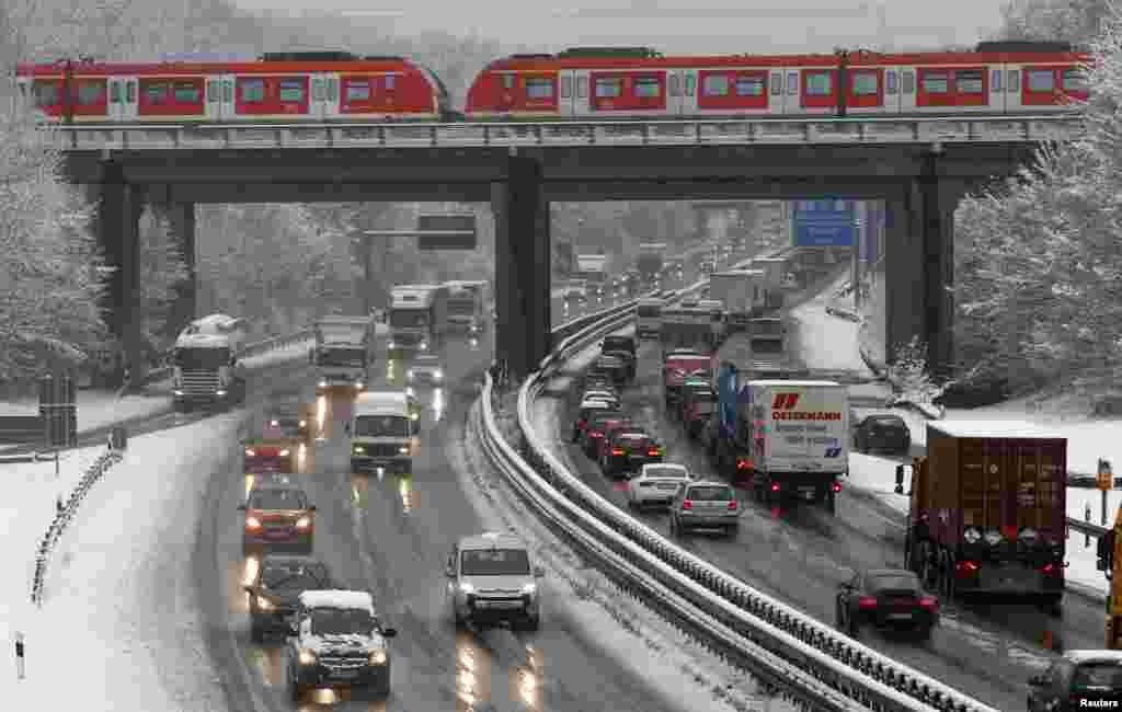 Xe cộ chạy chậm chạp trên xa lộ phủ tuyết ở Bochum, Đức. Tuyết rơi dày, khiến cho trên 600 km đường xa lộ trong tuyến North-Rhine Westphalia bị tắt nghẽn.