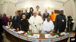 In this photo provided by Vatican newspaper L'Osservatore Romano, Pope Francis, center, and from left, Rabbi Abraham Skorka, Venerable Bhikkhuni Thich Nu Chan Khong, Her Holiness Mata Amritanandamayi and Undersecretary of State of Al Azhar Alsharif, Abbas Abdalla Abbas Soliman, pose after the signing a joint Declaration of Religious Leaders against Modern Slavery, at the Vatican, Dec. 2, 2014.