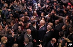 FILE - Then-Republican presidential candidate Donald Trump, center right, says goodbye to Dr. Darrell Scott, foreground left center, the senior pastor of New Spirit Revival Ministries in Cleveland Heights, Ohio, surrounded by media in the lobby of Trump Tower in New York, after meeting a coalition of 100 African-American evangelical pastors and religious leaders, Nov. 30, 2015.