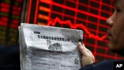 Seorang pria memegang surat kabar sambil mengamati papan elektronik yang menampilkan harga-harga saham di lantai bursa di Beijing (5/12). (AP/Andy Wong)
