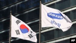 The company flag of Samsung Electronics (right) flutters next to the South Korean national flag in Seoul, South Korea, Jan. 16, 2017.