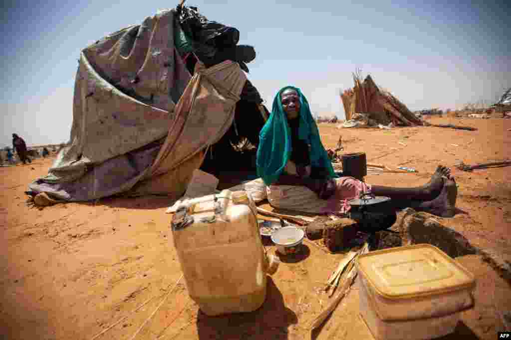 A handout picture released by the United Nations-African Union Mission in Darfur (UNAMID) shows Aisha Abdala, a displaced woman from Katila, South Darfur, cooking next to her shelter at the al-Sereif camp for Internally Displaced Persons (IDP) in Nyala, South Darfur, Sudan.