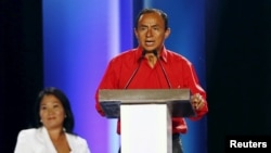 FILE - Peru's presidential candidate Gregorio Santos speaks next to candidate Keiko Fujimori (L) at a presidential debate in Lima, April 3, 2016. Santos accuses the government of locking him up for two years in order to keep him from power.