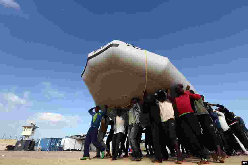 Migrants carry a raft, after being rescued by the Libyan coastguard, at a naval base near the capital Tripoli, Libya. The bodies of 85 migrants have been found washed up on the coast of Libya, a major departure point for the sea crossing to Europe, the Red Crescent said.