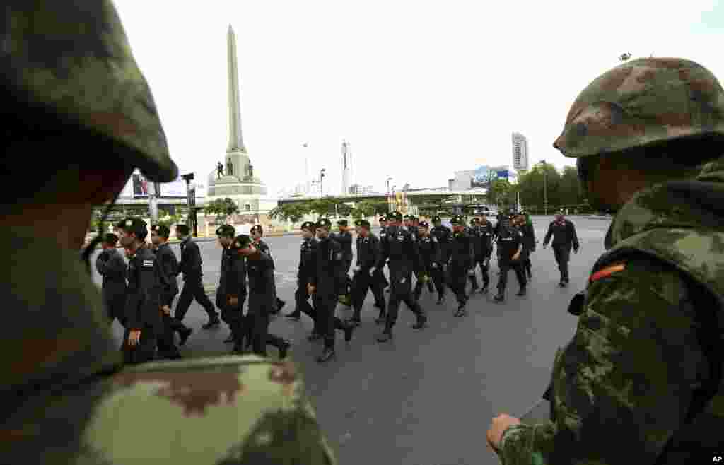 Soldiers watch as police officers are reinforced to prevent an anti-coup demonstration at the Victory Monument in Bangkok, May 29, 2014.