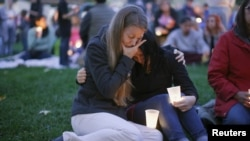 Sisters Heidi Wickersham, left, and Gwendoline Wickersham join in a vigil Saturday for those killed two days earlier at Umpqua Community College, near Roseburg, Ore. The gunman killed nine people before committing suicide, Oct. 1, 2015.