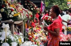 A woman buys flowers at a market on Valentine's Day in Harare, Zimbabwe, Feb. 14, 2017.