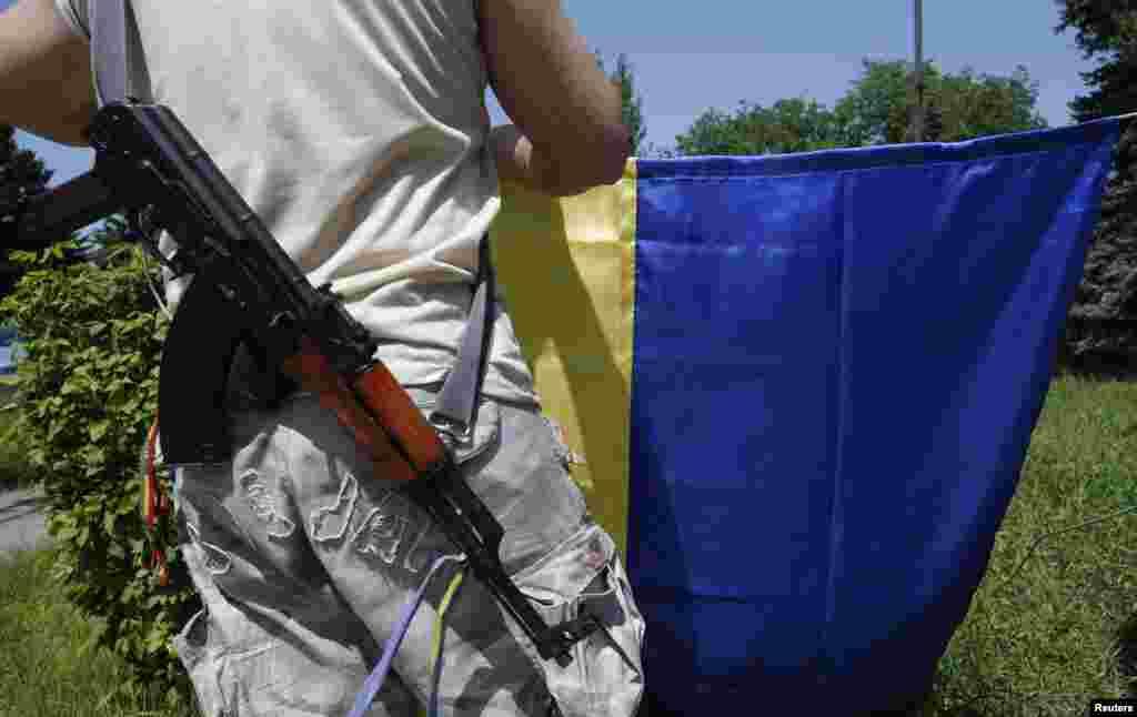 A pro-Ukrainian activist prepares to hoist the Ukrainian flag in the town of Velika Novosyolka, in the Dontesk region, eastern Ukraine, May 17, 2014.