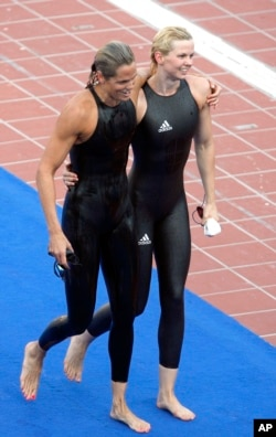 FILE - Germany's Britta Steffen, right, walks off with Dara Torres of the United States after winning a women's 50-meter freestyle final at the FINA Swimming World Championships in Rome, Aug. 2, 2009. Swimsuit design wars culminated with a ludricrous display of speed at the 2009 championships.