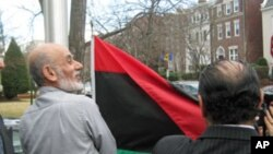 Activists raise the Libyan independence flag outside the Libyan ambassador's home in Washington, D.C., February 25, 2011