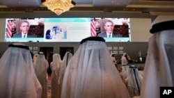FILE - Emirati officials watch U.S. President Barack Obama's keynote address at the opening ceremony of the World Government Summit in Dubai, United Arab Emirates.