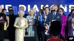 Britain's Prince Charles and Queen Elizabeth II are joined on stage with the rest of the Royal family as well as performers at the Queen's Jubilee Concert in front of Buckingham Palace, London, June 4, 2012.