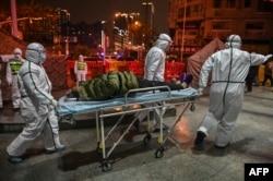 2020年1月25日穿着防护服的医务人员带着病人到达武汉红十字会医院。