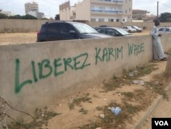 "A spray-painted message reads, ""Free Karim"" and is a common sight in the area as the trial of the former interior minister, Karim Wade, continues, Dakar, Senegal, Nov. 11, 2014. (Christin Roby/VOA)"