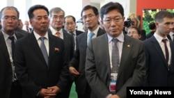 러시아 정부가 극동지역 개발에 필요한 외국 투자 유치를 위해 개최한 '동방경제포럼' 행사장에서 3일 윤상직 한국 산업통상자원부 장관(오른쪽 두번째)과 리용남 북한 대외경제상(왼쪽 두번째)이 주최 측의 설명을 듣고 있다.