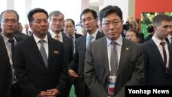 지난해 9월 러시아 블라디보스토크에서 열린 '동방경제포럼' 행사장에서 리용남 북한 대외경제상(왼쪽 2번째)과 윤상직 한국 산업통상자원부 장관(3번째)이 나란히 한 전시관 관계자의 설명을 듣고 있다. (자료사진)