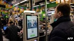 Perwakilan grup X5 mendemonstrasikan sistem pembayaran dengan teknologi pengenalan wajah di mesin kasir mandiri di supermarket Perekrestok, Moskow, Rusia, 9 Maret 2021. (Foto: Dimitar DILKOFF / AFP)