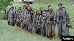 Kurdistan Workers Party (PKK) fighters walk on the way to their new base in northern Iraq, May 14, 2013.