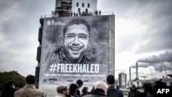 Orang-orang menghadiri pemasangan terpal yang menggambarkan jurnalis yang dipenjara Khaled Drareni di Paris, 15 Oktober 2020. (Foto: AFP)