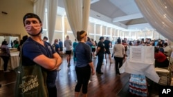 Voters wait in line to cast their ballots in the state's primary election at a polling place, Tuesday, June 9, 2020, in Atlanta, Ga. Some voting machines went dark and voters were left standing in long lines in humid weather as the waiting game…