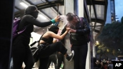 Two women assault a commuter, one spraying him in the face with paint another kicking him, at a bus station, during a protest sparked by a string of alleged sexual attacks by police officers, in Mexico City, Friday, Aug. 16, 2019.