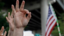 """Dalam sebuah foto yang diambil pada 17 Agustus 2019 ini, tampak anggota dari kelompok sayap kanan di Amerika Serikat menunjukkan gestur tangan 'OK' yang mengacu pada supremasi kulit putih dalam sebuah demonstrasi """"The End Domestic Terrorism"""" di Oregon. (Foto: AFP/John Rudoff)"""
