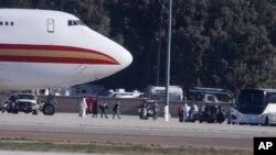 Warga AS yang dievakuasi dari Wuhan, China masuk ke dalam bus, China, setibanya di Pangkalan Udara di Riverside, California, 39 Januari 2020.
