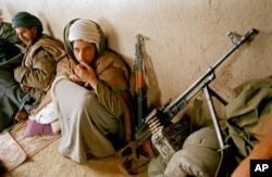 FILE - Taliban fighters huddle in a front line shelter during a lull in fighting south of Kabul, Afghanistan, March 22, 1995.