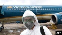 Tư liệu: Ảnh chụp ngày 3/3/2020 nhân viên chuẩn bị khử trùng một chiếc máy bay của Vietnam Airlines ở sân bay Nội Bài, Hà Nội. AFP