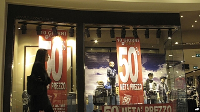 A woman walks past the window of a clothes store announcing 50 percent discounts in downtown Milan, Italy, November 7, 2011.