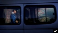 A North Korean traffic police woman is framed by a window of a passing vehicle as she walks past commuters waiting at a bus stop at the end of a workday on Monday, Oct. 17, 2016, in Pyongyang, North Korea.