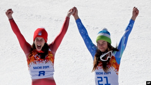 Women's downhill gold medal winners Switzerland's Dominique Gisin, left, and Slovenia's Tina Maze stand together on the podium during a flower ceremony at the Sochi 2014 Winter Olympics, Wednesday, Feb. 12, 2014.