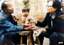 This undated photos shows retired doctor Gao Yaojie, 74, right, applying medicine to a villager's arm as she helps people from neglected AIDS villages in the central China province of Henan.