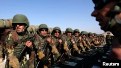 FILE - Afghan soldiers take their oaths before a training exercise at the Kabul Military Training Center, Oct. 22, 2014.