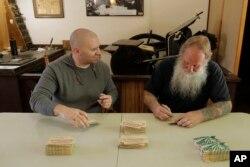 Loren Ackerman (kanan) dan Wali Kota Tenino Wayne Fournier (kiri) menandatangani uang-uang kayu yang dicetak Ackerman dengan alat cetak dari 1890an, di Tenino, Washington, 21 Mei 2020. (Foto: AP)