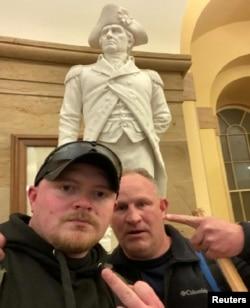 弗吉尼亚州的两位下班警察弗拉克和罗伯逊在冲击国会大厦期间自拍合影并摆出侮辱性的手势。